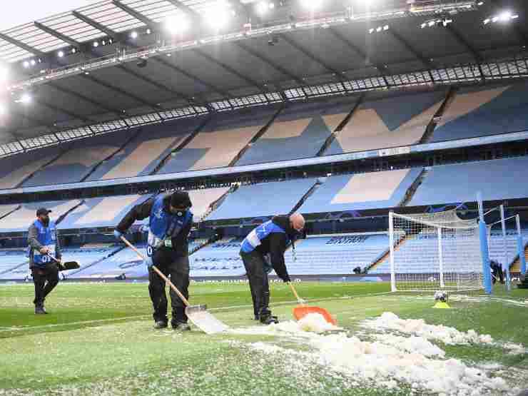 Etihad Stadium, il campo viene pulito dalla grandine che ha rovinato il campo da gioco prima dell'inizio del primo tempo della semi-finale di Champions League Manchester City-PSG. 4 maggio 2021 (foto di Laurence Griffiths/Getty Images).